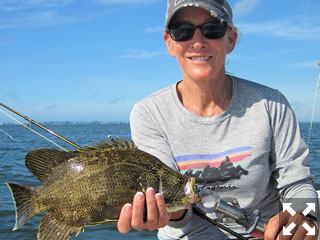 Sunny Moss, from Sarasota, with a tripletail caught and released on a fly on her first fly fishing trip.