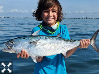 Eight-year-old Ryan McTeadue with a bonita he caught fishing out of CB's Saltwater Outfitters with Capt. R.C. Gilliland.