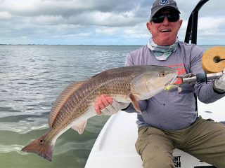 Marshall Dinerman, from Lido Key, with an over-slot red caught and released on a CAL jig with a shad tail while fishing shallow water with Capt. Rick Grassett.