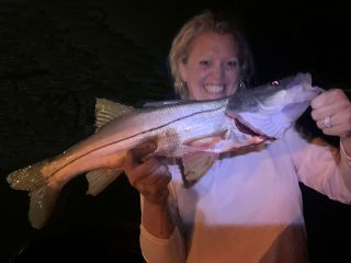 Shara King, from Dillon, MT, with a nice snook caught and released on a fly while fishing at night with Capt. Rick Grassett.