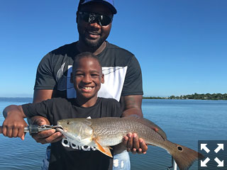 Nyghee, and his son Nyghee Jr. with a nice sized Redfish they caught fishing Sarasota Bay this past week.