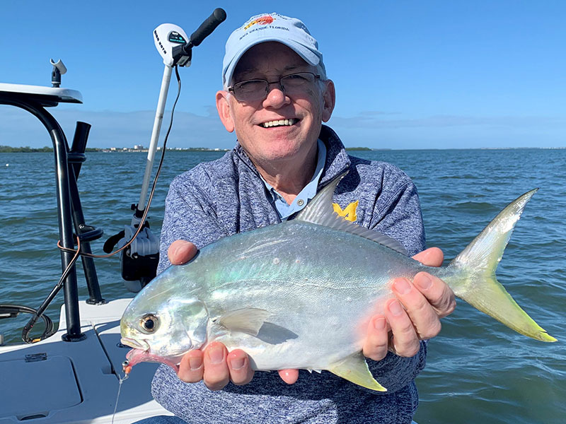 Ray Hutchinson, from MI, with a pompano caught on a Clouser fly while fishing deep grass flats of Sarasota Bay with Capt. Rick Grassett in a previous December.