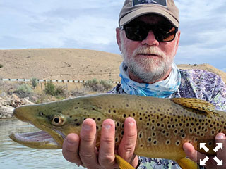 Capt. Rick Grassett with a nice brown trout caught and released on a fly while fishing with King Outfitters out of Dillon, MT.
